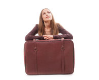 Ragazza che si siede vicino ad una valigia, isolata sul bianco immagini stock libere da diritti