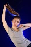 Ragazza che si tira dai capelli su fondo blu Fotografie Stock