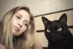 Ragazza che si trova a letto con il suo gatto fotografia stock libera da diritti