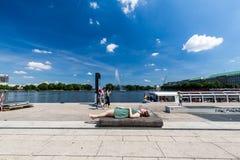 Ragazza che si trova su un banco al Jungfernstieg a Amburgo, Germania Immagini Stock Libere da Diritti