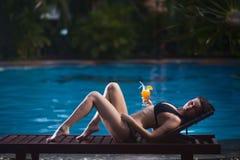 Ragazza che si trova su una chaise-lounge del sole sui precedenti dello stagno di estate all'aperto e che tiene succo d'arancia i fotografia stock