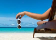 Ragazza che si trova su una chaise-lounge della spiaggia con i vetri a disposizione Fotografia Stock