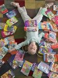 Ragazza che si trova sul pavimento con i libri sparsi intorno Fotografia Stock
