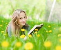 Ragazza che si trova sull'erba con i denti di leone che legge un libro Fotografia Stock Libera da Diritti