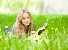 Ragazza che si trova sull'erba con i denti di leone che legge un libro e che esamina macchina fotografica Immagine Stock