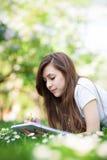 Ragazza che si trova sull'erba con il libro di esercizi Immagine Stock