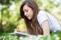 Ragazza che si trova sull'erba con il libro di esercizi e la matita Immagini Stock Libere da Diritti
