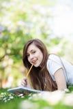 Ragazza che si trova sull'erba con il libro di esercizi e la matita Fotografie Stock Libere da Diritti