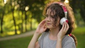 Ragazza che si trova sull'erba e che ascolta la musica sulle cuffie Il piccolo bambino caucasico sveglio sta divertendosi la refr stock footage