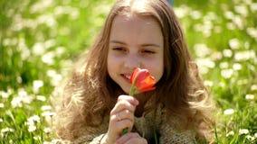Ragazza che si trova sull'erba, grassplot su fondo Concetto di fragranza del tulipano La ragazza sul fronte sorridente tiene il f video d archivio
