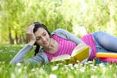 Ragazza che si trova sull'erba in sosta con il libro e la cuffia avricolare Fotografia Stock Libera da Diritti