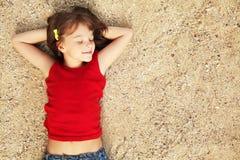 Ragazza che si trova sulla sabbia Immagini Stock