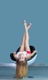 Ragazza che si trova sulla sedia sottosopra Fotografie Stock