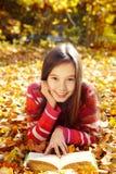 Ragazza che si trova sulle foglie cadute e che legge un libro Fotografia Stock