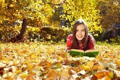 Ragazza che si trova sulle foglie cadute e che legge un libro Immagine Stock