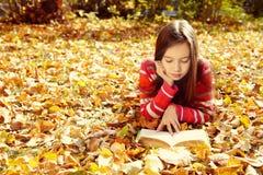 Ragazza che si trova sulle foglie cadute e che legge un libro Immagini Stock