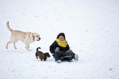 Ragazza che sledging con il suo cane Fotografie Stock