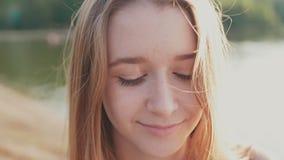 Ragazza che sorride con il sorriso perfetto ed i denti bianchi in un parco e che esamina macchina fotografica archivi video