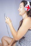 Ragazza che sorride con il telefono e le cuffie Fotografia Stock