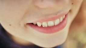 Ragazza che sorride con un diamante su un dente Skyce sui denti Piercing dentario del diamante archivi video