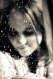 Ragazza che sorride dietro una finestra piovosa al sole immagini stock