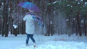 Ragazza che sorride e che balla con l'ombrello nella foresta della neve stock footage