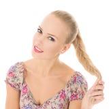 Ragazza che sorride e che gioca con i suoi capelli/ragazza bionda fotografia stock libera da diritti