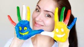 Ragazza che sorride e che mostra le mani sporche dipinte con i sorrisi Il concetto di felicità, di buon umore e di gioia video d archivio