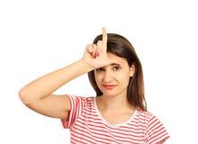 Ragazza che sorride mostrando il segno del perdente sulla fronte ragazza emozionale isolata su fondo bianco Fotografia Stock