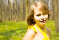 Ragazza che sorride nel giacimento pieno di sole della sorgente. Copi lo spazio Fotografia Stock