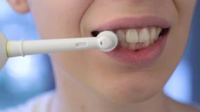 Ragazza che spazzola il suo spazzolino da denti elettronico dei denti stock footage