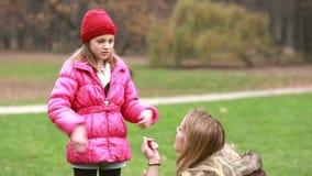 Ragazza che spiega gioco alla sua mamma in parco, papà che viene e che la abbraccia archivi video