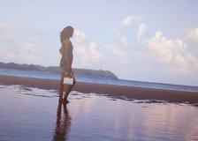 Ragazza che sta in acqua su una spiaggia Fotografie Stock Libere da Diritti