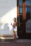 Ragazza che sta al sole vicino alla costruzione Fotografie Stock Libere da Diritti