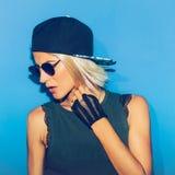 Ragazza che sta alla parete blu in vetri e cappuccio alla moda porcile urbano fotografia stock libera da diritti