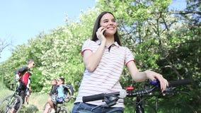 Ragazza che sta con la bicicletta e che chiacchiera sul cellulare archivi video