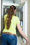 Ragazza che sta frigorifero vicino Fotografie Stock