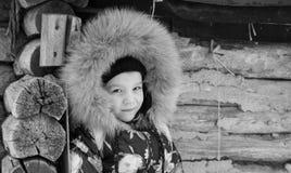 Ragazza che sta nell'inverno vicino alla vecchia casa di legno Fotografie Stock Libere da Diritti