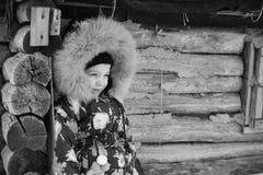 Ragazza che sta nell'inverno vicino alla vecchia casa di legno Fotografia Stock Libera da Diritti