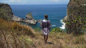 Ragazza che sta su una scogliera e che esamina il mare Bali, Indonesia fotografia stock libera da diritti