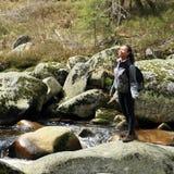 Ragazza che sta sulla roccia tramite la corrente dell'acqua Immagine Stock