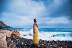 Ragazza che sta sulla spiaggia contro il cielo ed il mare Fotografia Stock