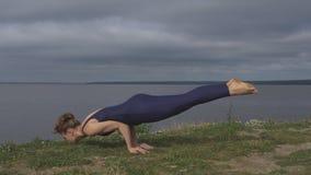Ragazza che sta sulle mani, addestramento dell'equilibrio di yoga video d archivio