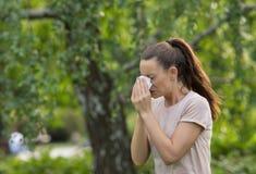 Ragazza che starnutisce nel parco a causa dell'allergia del polline Fotografie Stock Libere da Diritti