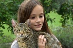 Ragazza che stringe a sé con il suo gatto fotografie stock libere da diritti