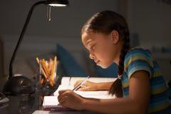 Ragazza che studia allo scrittorio in camera da letto nella sera Fotografia Stock