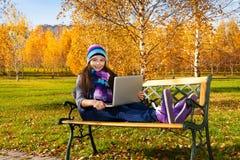 Ragazza che studia fuori con il computer portatile Fotografie Stock Libere da Diritti