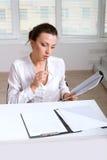 Ragazza che studia i documenti che si siedono alla tavola Immagini Stock