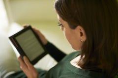 Ragazza che studia letteratura con il libro elettronico a casa immagine stock