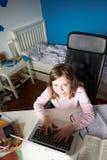 Ragazza che studia nella camera da letto facendo uso del computer portatile Fotografie Stock